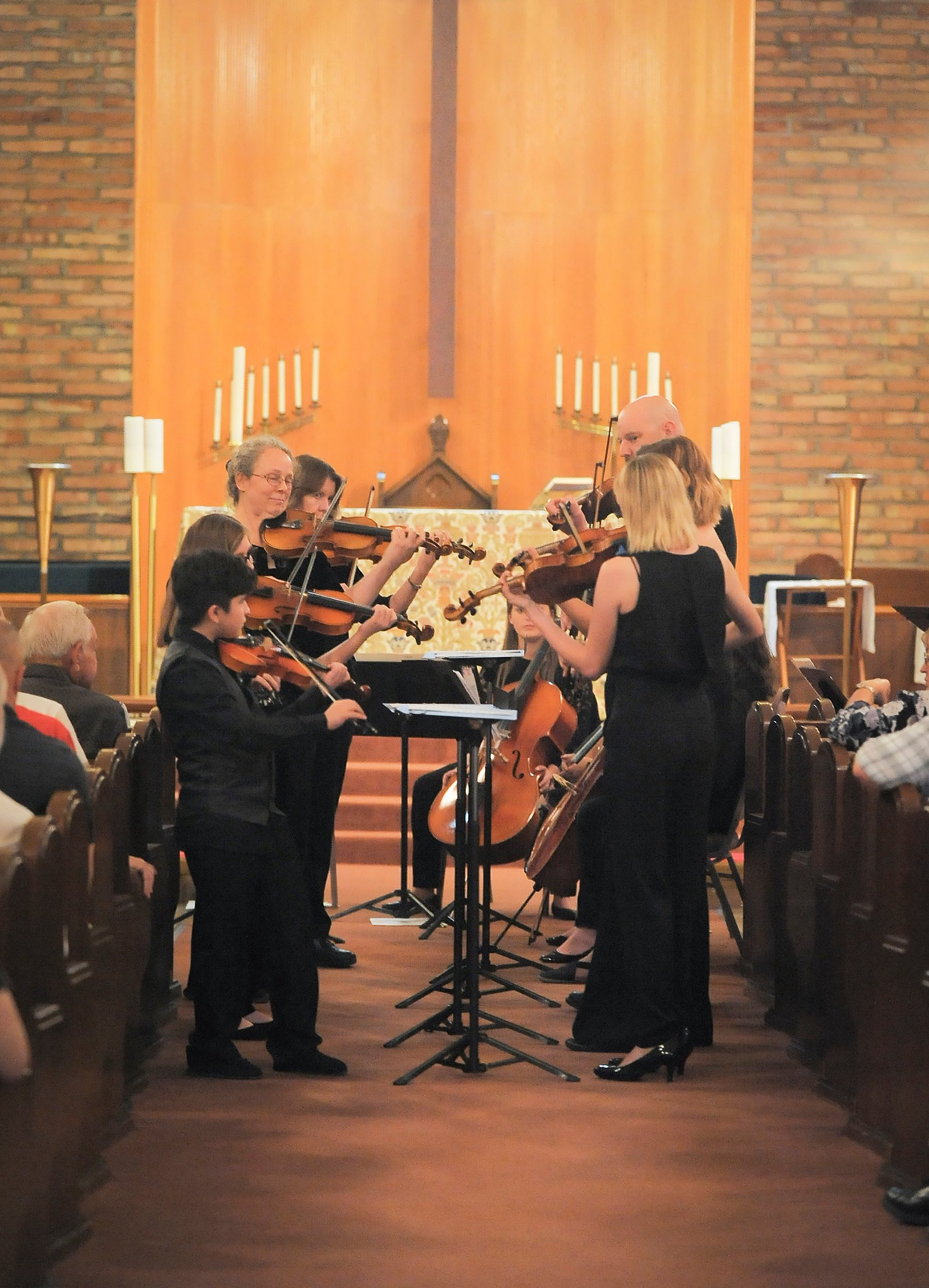 Performers stand playing string instruments in a church