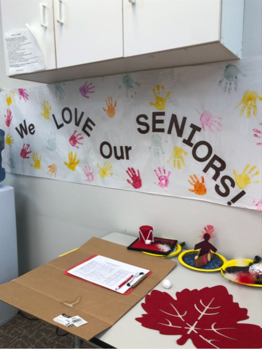 """Decorated office space with painted handprints and text that reads """"We love our seniors!"""""""