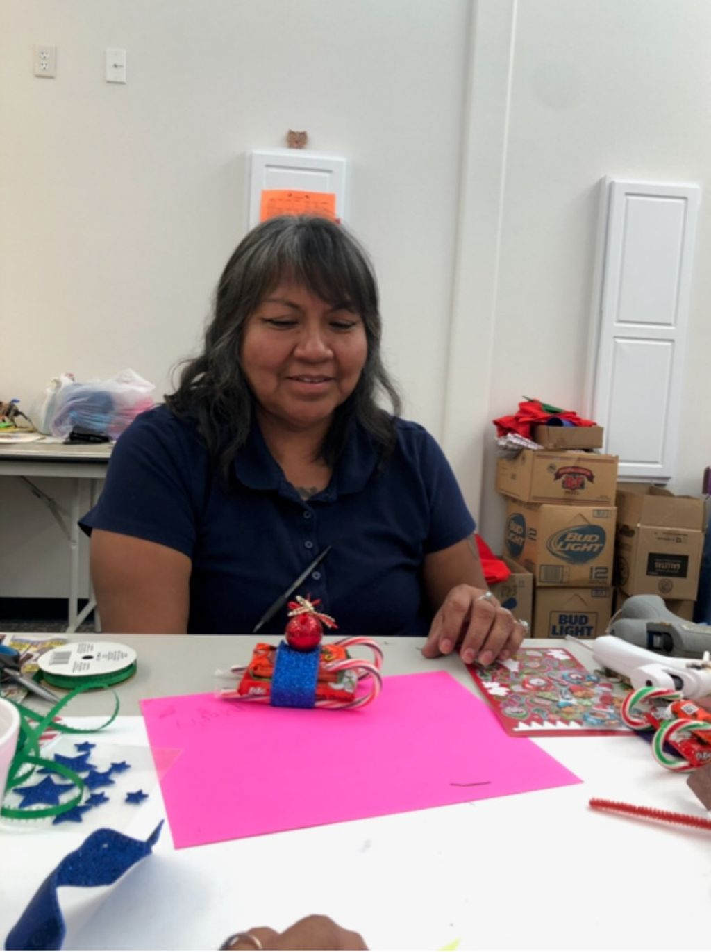 An older woman smiles down at a little craft