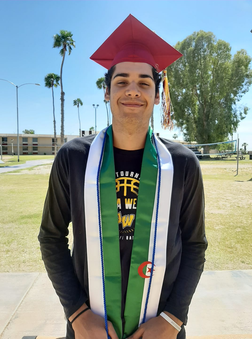 A graduate stands wearing sashes and a cap in front of the AWC dorms
