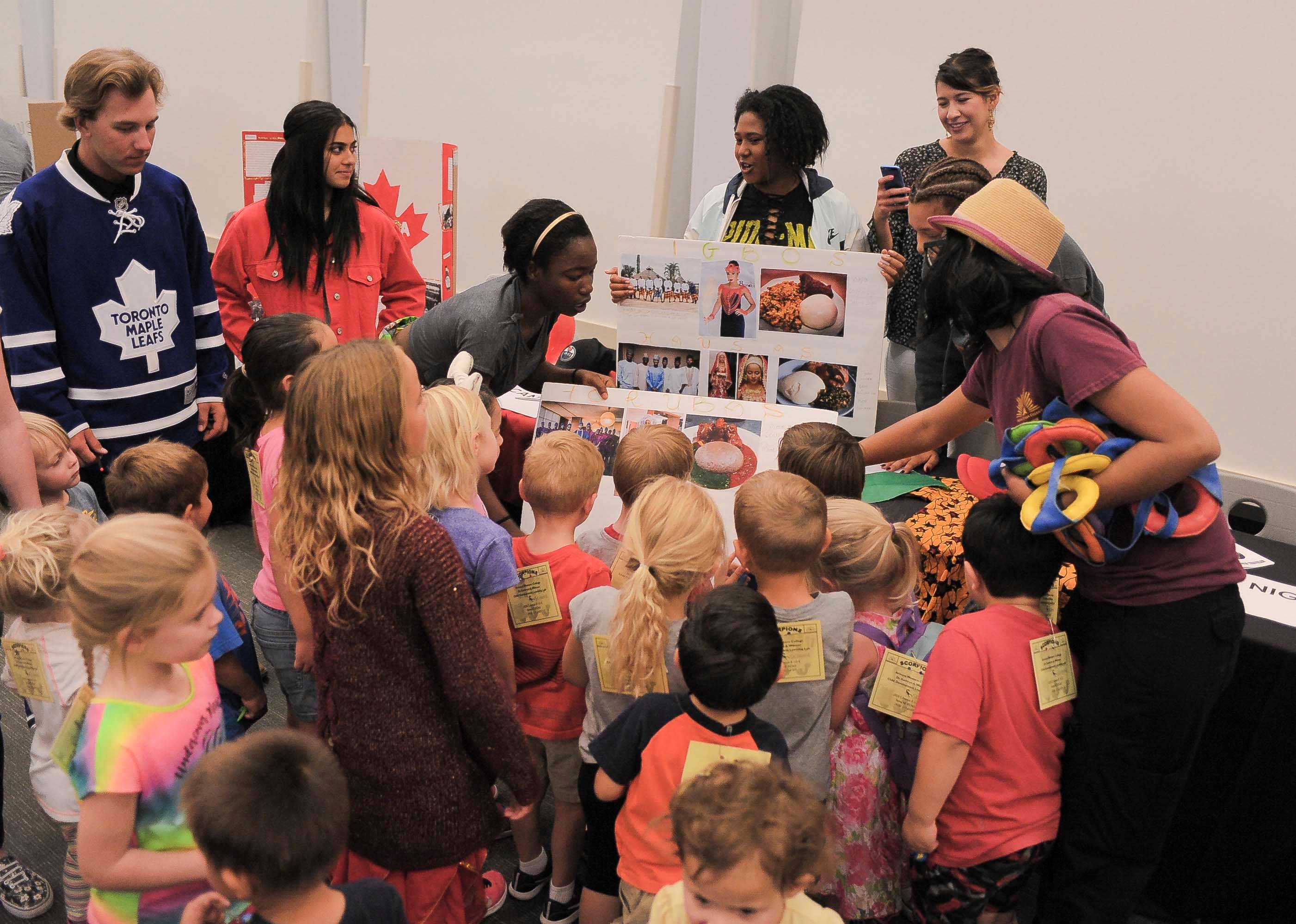 Young children are gathered around a display as AWC students explain various images.