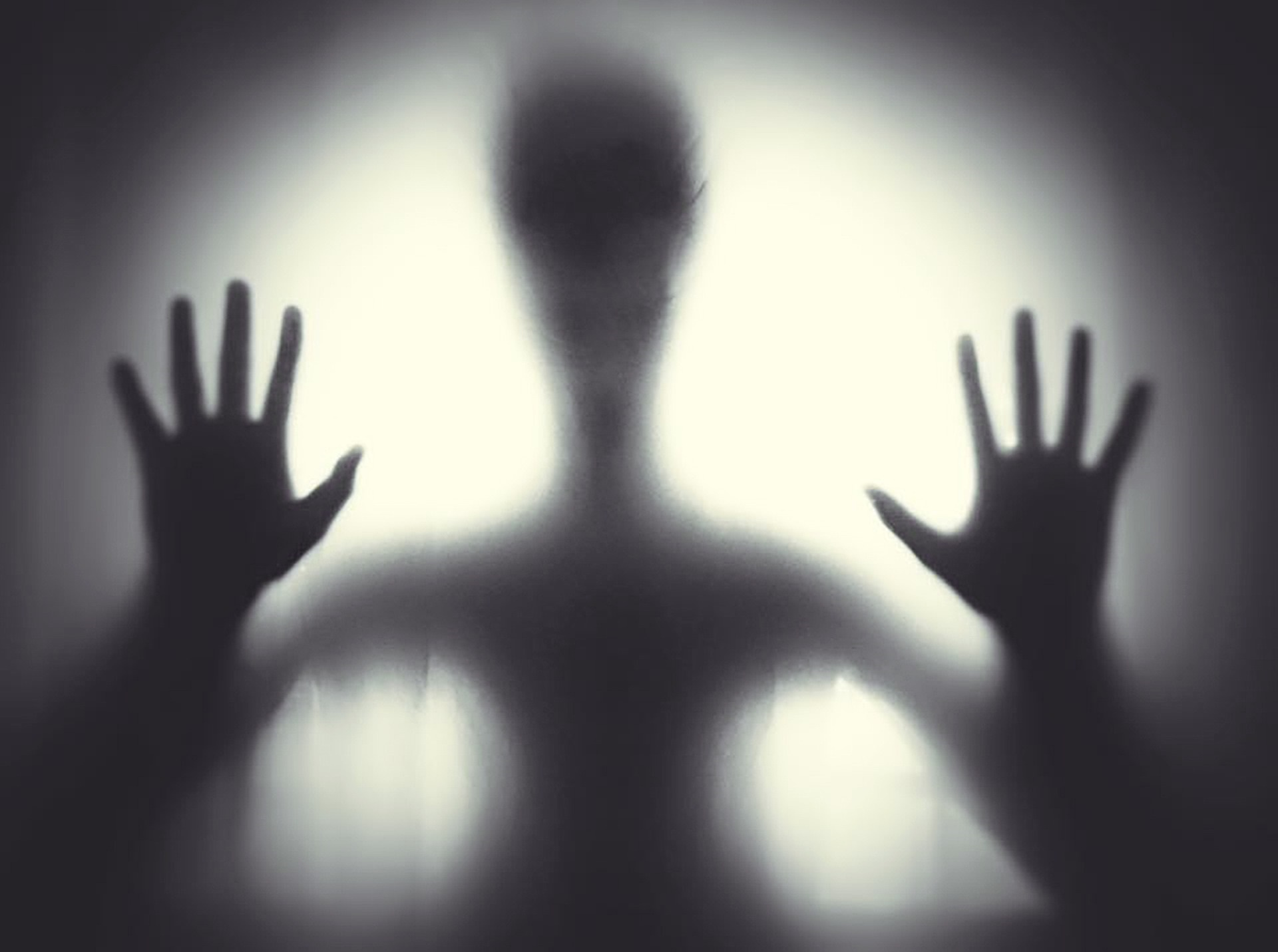 A silhouette of a person with their hands on the screen is illuminated ominously
