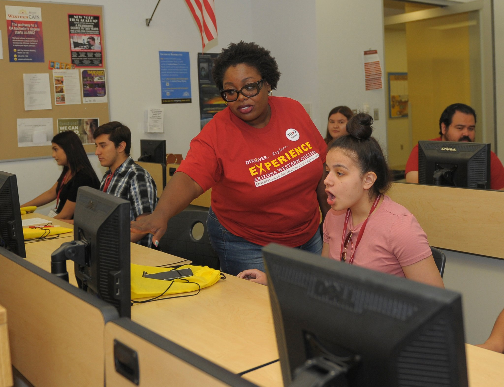 African-American woman points to a computer screen as she helps a student.
