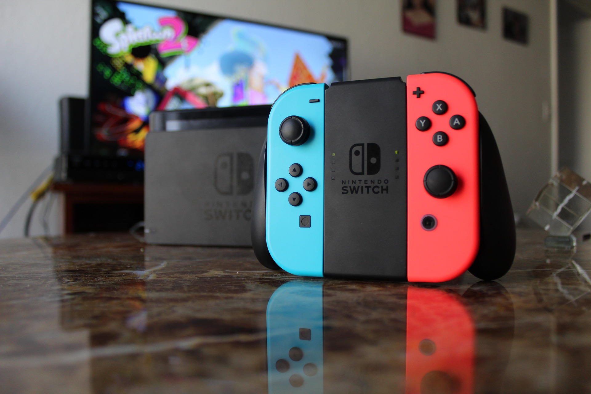 A nintendo switch piece with blue and red sides sits on a dark marble countertop with a video game screen in the background