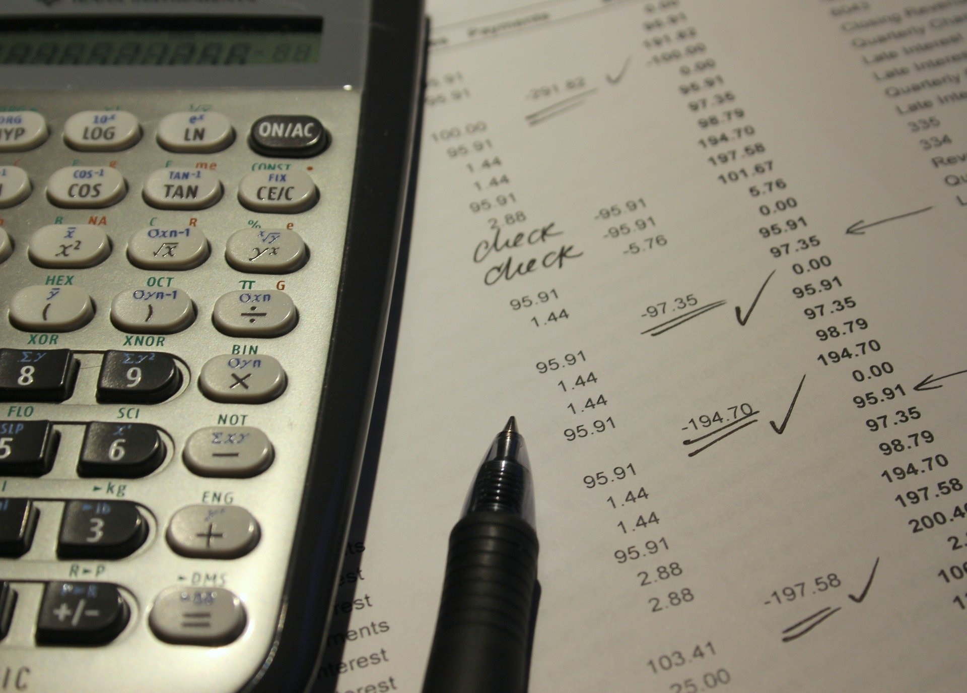 A calculator and pen sit atop a paper used for finance checking