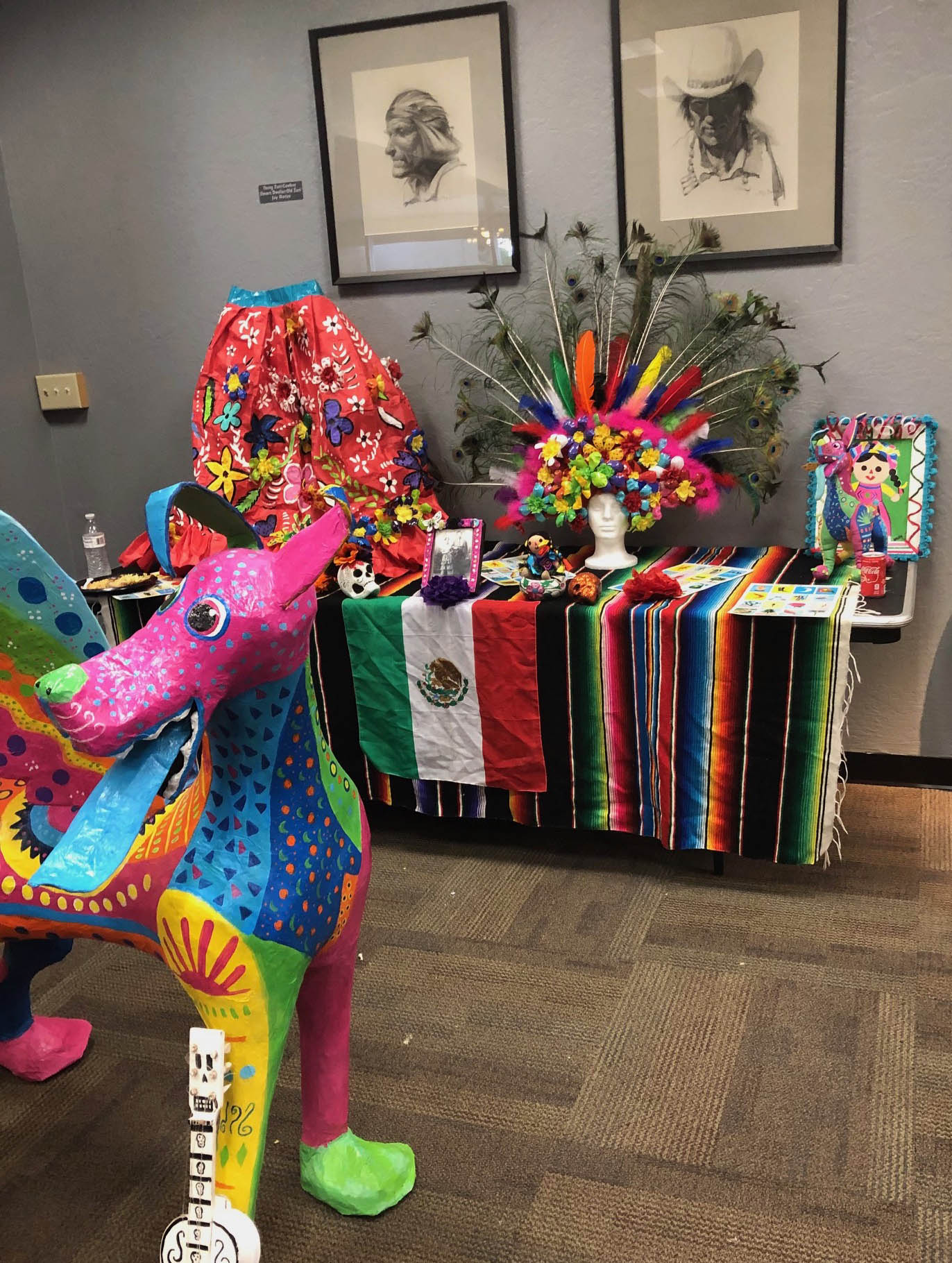 Colorful dog-like sculpture in front of a Mexican heritage display.