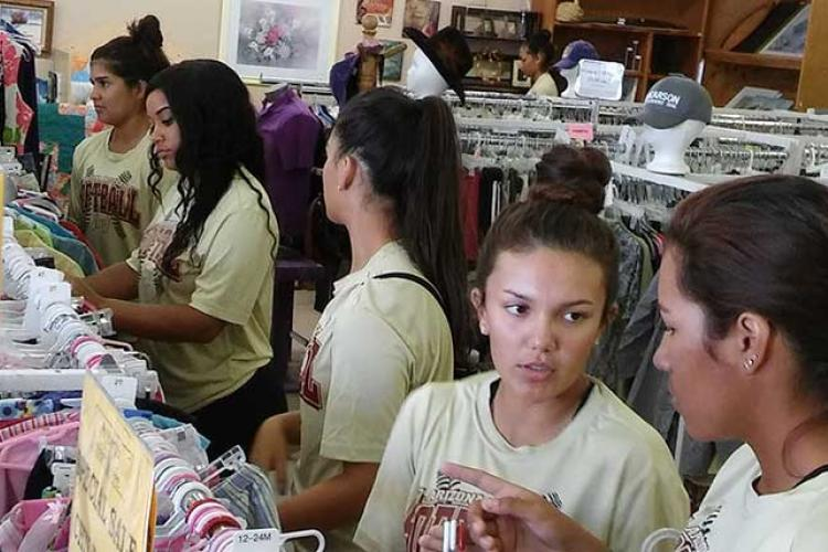 Softball players volunteered at Amberly's Place Thlrift Shoppe.