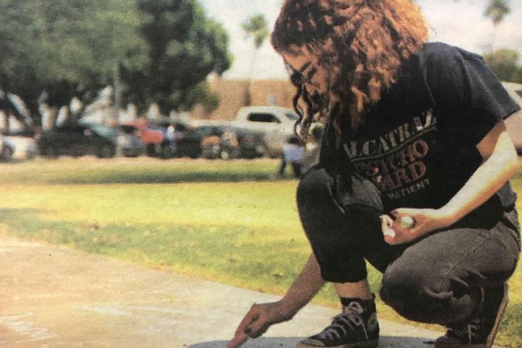 Student kneels down to write with chalk on school sidewalk