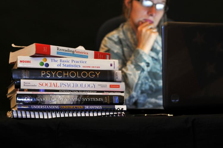 college books in front of a soldier looking into a computer.