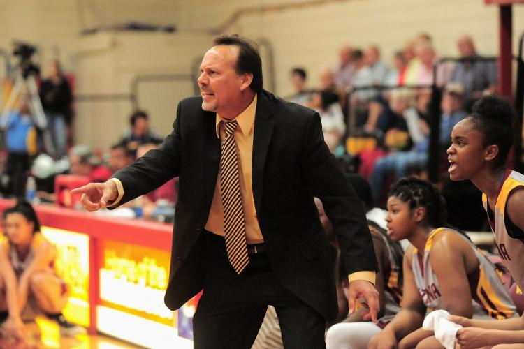 Coach Cunningham is dressed in a black suit and tie, seen yelling towards off-frame players. He is standing inside a sports game in the Basketball court
