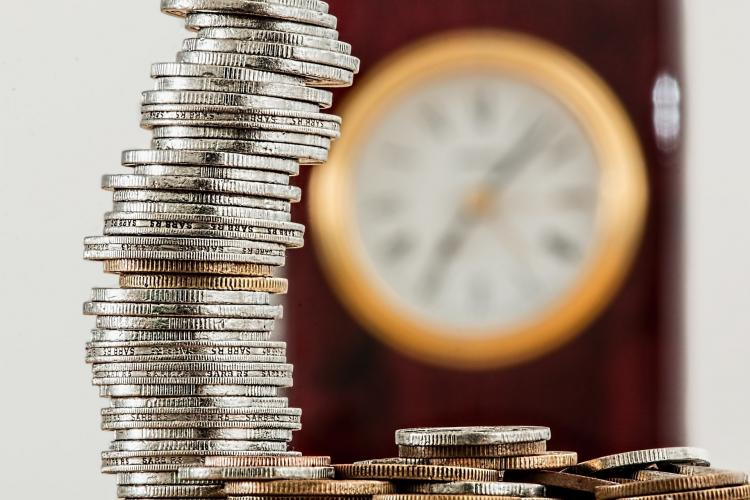 Quarters are stacked in an imperfect column with a gold-accented clock blurred in the background