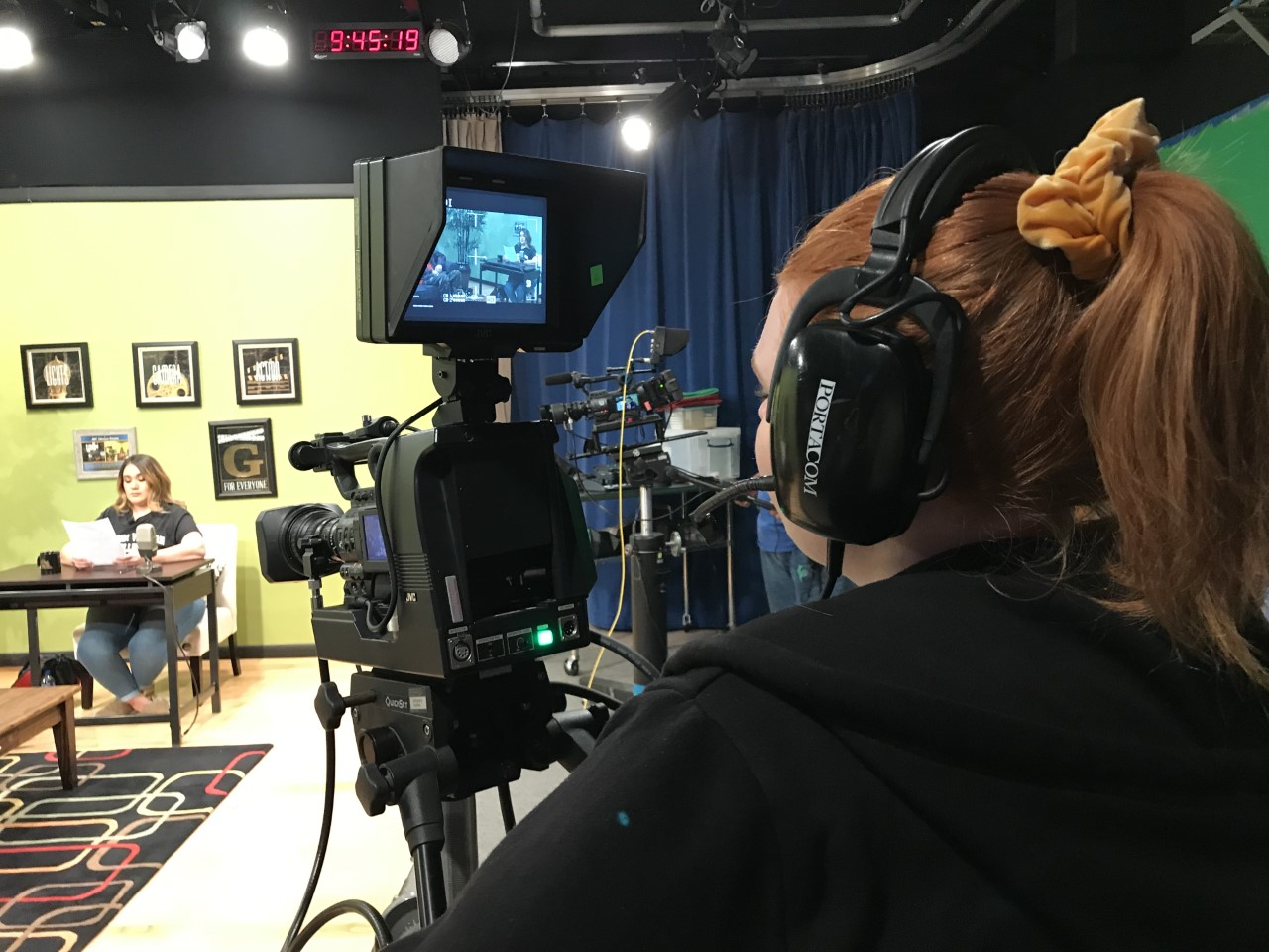 A person stands behind a camera with headphones on, recording the show